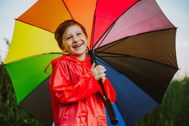 Портрет улыбающегося школьника с радужным зонтиком в парке. ребенок держит красочный зонтик на