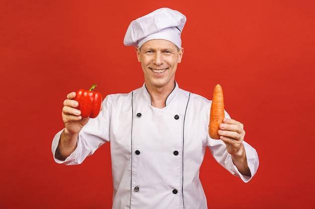 Портрет усмехаясь старшего кашевара шеф-повара держа морковь и красный пеец изолированный на красной предпосылке.