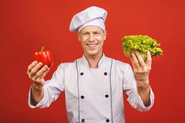Портрет усмехаясь старшего кашевара шеф-повара держа салат и красный пеец изолированный на красной предпосылке.