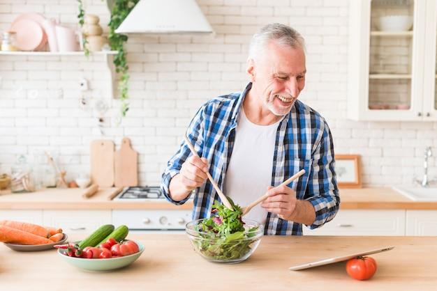 Портрет улыбающегося старшего человека, глядя на цифровой планшет, готовит салат на кухне
