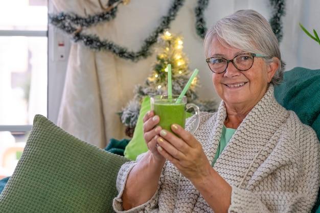 自家製の緑のスムージーのグラスを持って自宅のソファでリラックスした笑顔の年配の女性の肖像画。野菜や果物を使ったヘルシーなデトックスビーガンダイエット。背景のクリスマスの装飾
