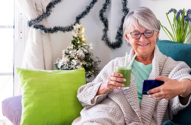 自家製の緑のスムージーのガラスを保持している彼女のスマートフォンを見ている自宅のソファでリラックスした笑顔の年配の女性の肖像画。野菜や果物を使ったヘルシーなデトックスビーガンダイエット。