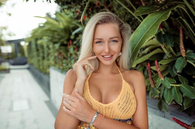 Портрет улыбающейся сексуальной блондинки с голубыми глазами в желтом топе с большой грудью, позирующей среди зеленой листвы