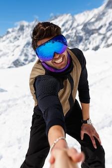 Портрет улыбающегося лыжника позирует перед камерой, держась за руку с фотографом