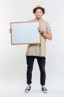Портрет улыбающегося стильного мужчины, держащего пустую доску, изолированную на белом фоне
