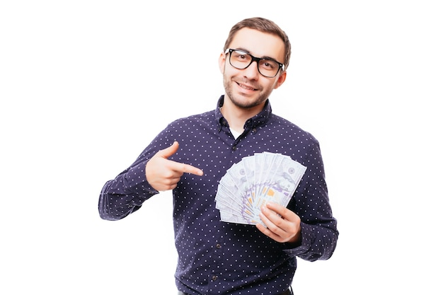 Портрет улыбающегося успешного человека в костюме и очках, указывающего пальцем на кучу денежных банкнот, изолированных на белой стене