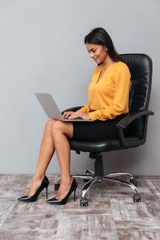 의자에 앉아 웃는 성공적인 여자의 초상화