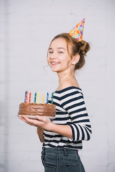 Portrait of a smiling teenage girl holding chocolate cake with colorful candles