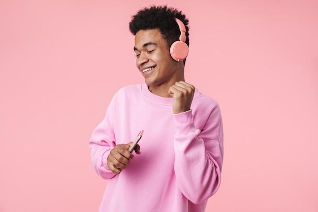 ピンクの壁の上に孤立して立っている、ヘッドフォンで音楽を聴いて、携帯電話を持って、踊っているpullowerを身に着けている笑顔のティーンエイジャーの少年の肖像画