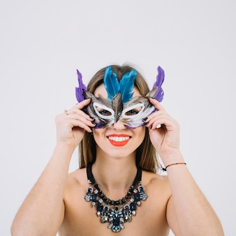 Portrait of a smiling topless woman wearing feather mask on white backdrop