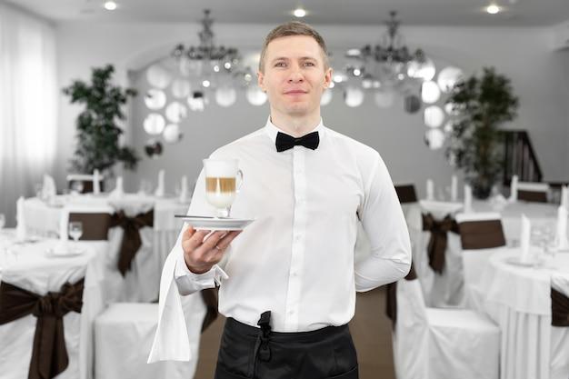 레스토랑에서 웃는 웨이터의 초상화, 그는 고객에게 라떼를 제공합니다.