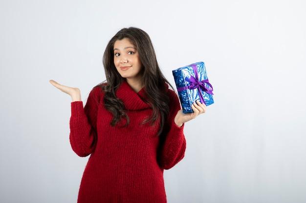 보라색 리본으로 크리스마스 선물 상자를 들고 웃는 여자의 초상화.
