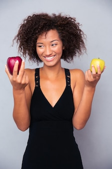 Портрет улыбающейся женщины, держащей яблоки над серой стеной