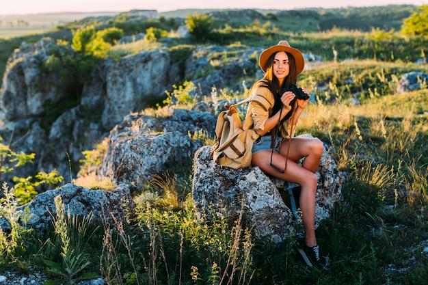Портрет улыбается женщина, бинокль, сидя на скале