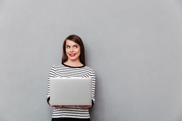 Портрет улыбается женщина, держащая портативный компьютер