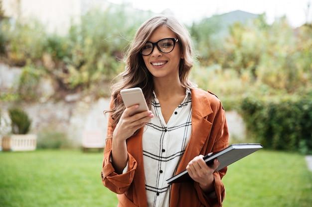 Портрет улыбающейся женщины, держащей мобильный телефон
