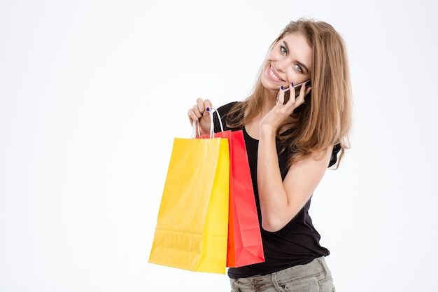 Портрет улыбающейся женщины, держащей хозяйственные сумки и говорящей по телефону, изолированной на белом фоне
