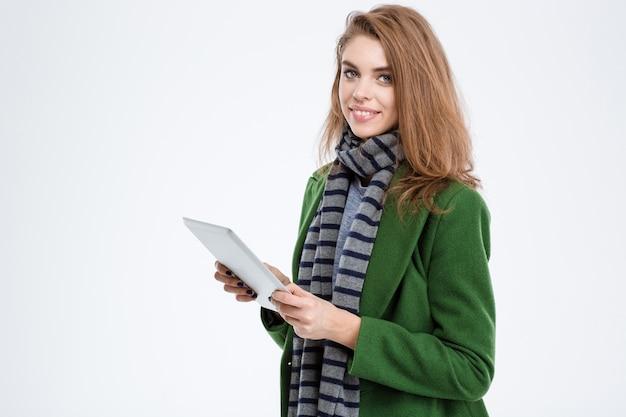 白い背景で隔離のタブレット コンピューターを押しながらカメラ目線の笑顔の女性の肖像画