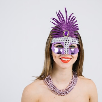 Portrait of a smiling woman in carnival mask wearing necklace over on white background