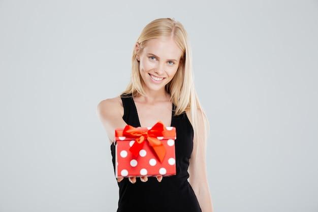 Портрет улыбающейся женщины в платье, держащей подарочную коробку, изолированную на белом фоне