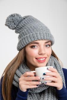 겨울 옷감 마시는 커피에 웃는 여자의 초상화는 흰색 배경에 고립