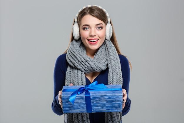 Портрет улыбающейся женщины в зимней ткани, держащей подарочную коробку на сером фоне