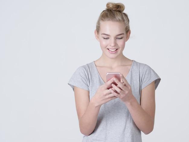 웃는 여자의 초상화는 스튜디오에서 휴대 전화에 문자 메시지를 입력합니다