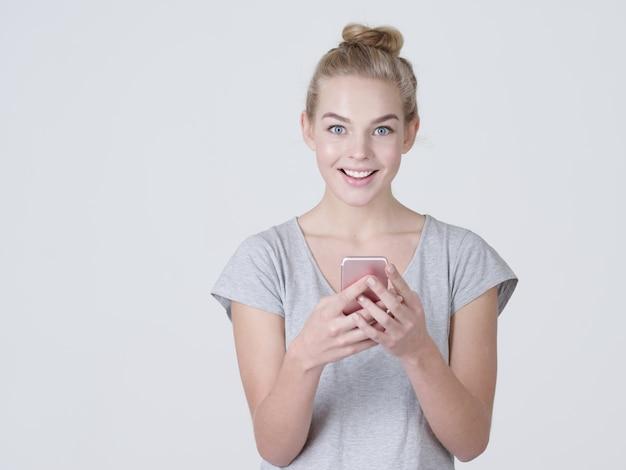笑顔の女性の肖像画が携帯電話でテキストメッセージを入力しています-スタジオで