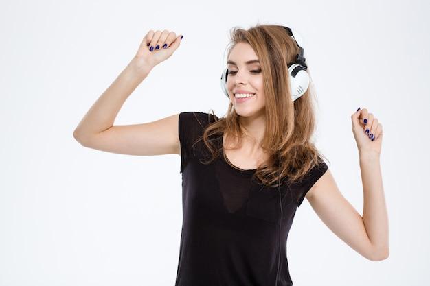 흰색 배경에 고립 된 헤드폰에 웃는 여자 듣는 음악의 초상화