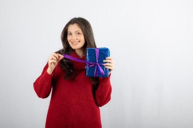 보라색 리본으로 크리스마스 선물 상자를 여는 웃는 여자의 초상화.