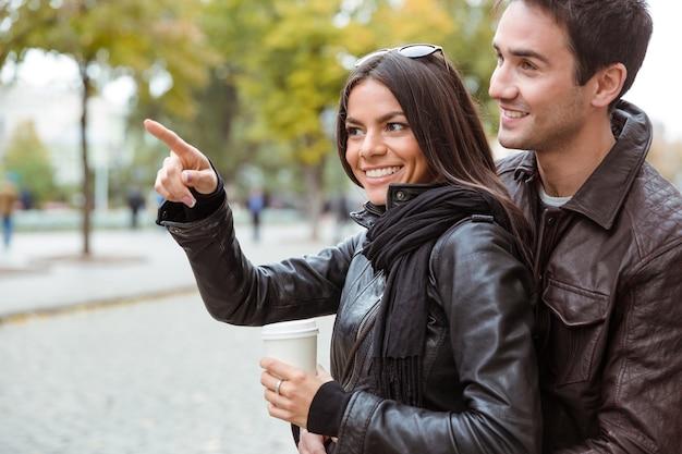 Портрет улыбающейся женщины, указывающей пальцем на что-то своему парню на открытом воздухе
