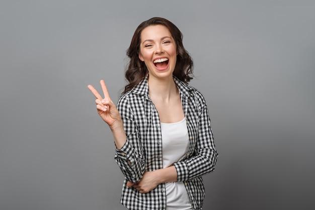 勝利のサインを示し、灰色で隔離のカメラをのぞきながら笑顔の女性の肖像画