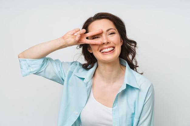 勝利のサインを示し、白で隔離のカメラをのぞきながら笑顔の女性の肖像画
