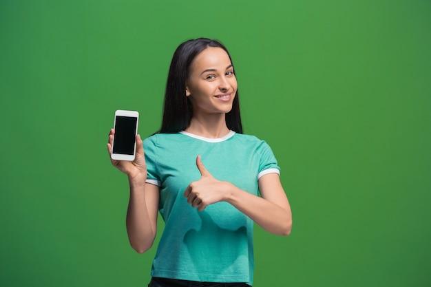 녹색 배경에 고립 된 빈 스마트 폰 화면을 보여주는 웃는 여자의 초상화