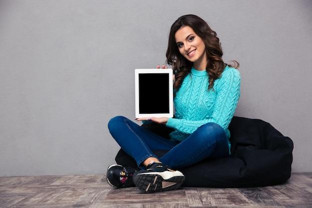 床に座って、灰色の壁の上の空白のタブレットコンピューター画面を示す笑顔の女性の肖像画