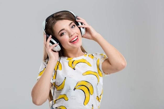 흰색 배경에 고립 된 카메라를보고 헤드폰으로 웃는 여자의 초상화