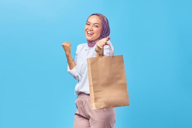 ショッピングバッグを示す笑顔の若いアラビアの大学生の肖像画
