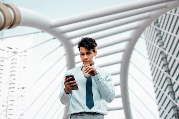 市内で携帯電話を使用して笑顔の若いasainビジネスマンの肖像画