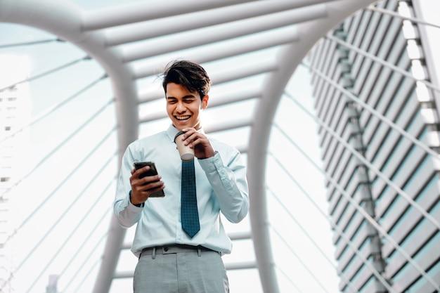 街で携帯電話を使用して笑顔の若いアジア人ビジネスマンの肖像画