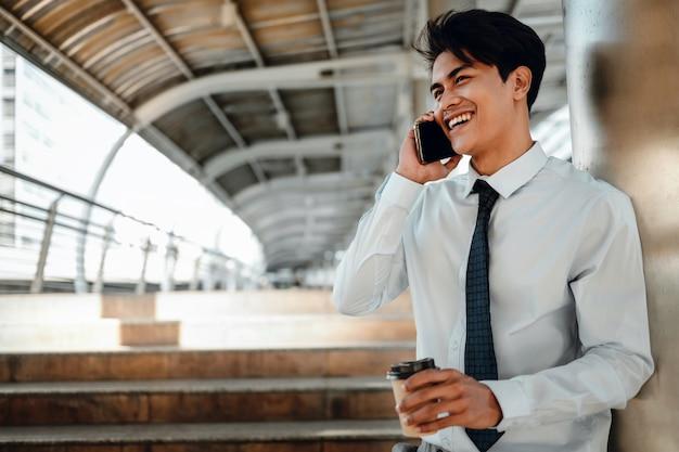 街で携帯電話を使用して笑顔の若いアジア人実業家の肖像画