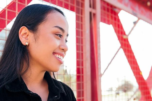 빨간 울타리에 기대어 야외에서 웃고 있는 젊은 아시아 여성의 초상화