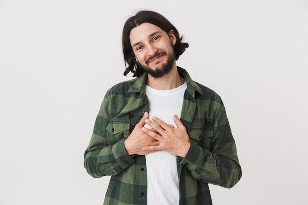 白い壁の上に孤立して立っている格子縞のシャツを着て笑顔の若いひげを生やしたブルネットの男の肖像画