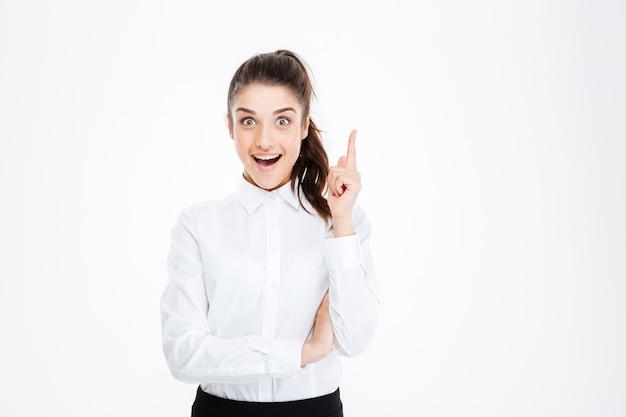 Портрет улыбающейся молодой красивой бизнес-леди, указывая пальцем вверх над белой стеной