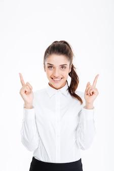 Портрет улыбающейся молодой красивой бизнес-леди, указывая пальцами вверх над белой стеной