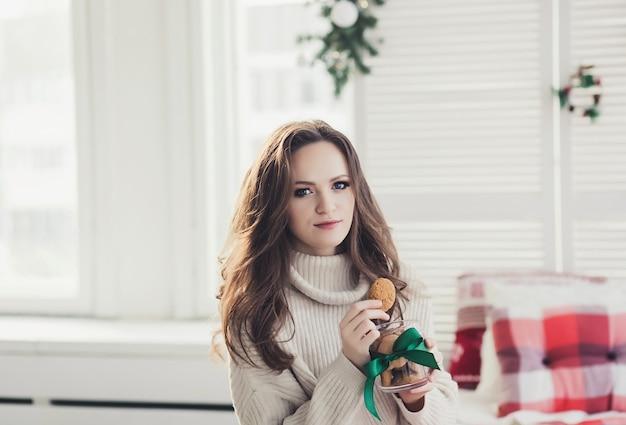 クッキーを食べる笑顔の若いブルネットの女性の肖像画