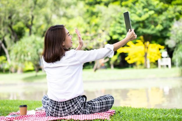 仕事の後にリラックスして公園で彼女の友人にビデオ通話のためにタブレットを使用して笑顔の若いビジネス女性の肖像画