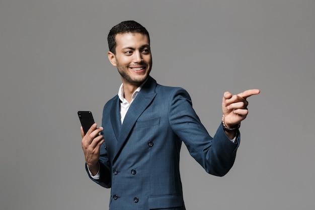 Портрет улыбающегося молодого бизнесмена, одетого в костюм, стоящего изолированно над серой стеной, держа мобильный телефон, указывая в сторону