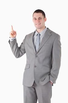 Портрет улыбающегося молодого бизнесмена, указывая на что-то