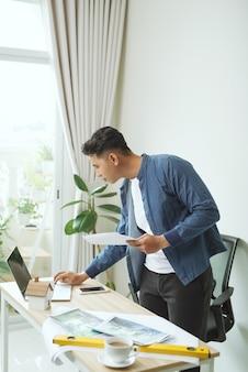 사무실에서 청사진 작업을 하는 웃고 있는 젊은 사업가의 초상화
