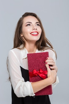 Портрет улыбающейся молодой деловой женщины, держащей подарочную коробку и смотрящей через серую стену